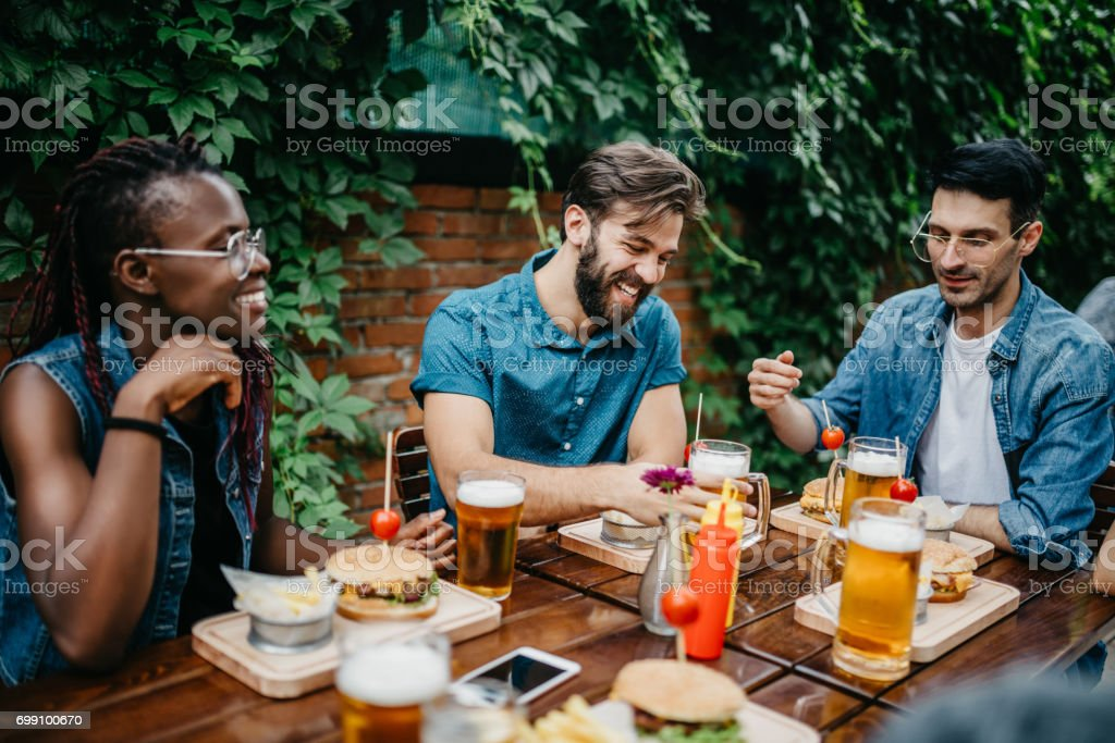 Happy multi-ethnic friends at the pub are having a lunch stock photo