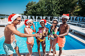 Happy multiethnic friends celebrating Christmas at pool party during vacation at resort