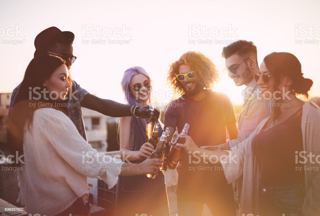 Happy multi-ethnic friends toasting with drinks at summer terrace party stock photo