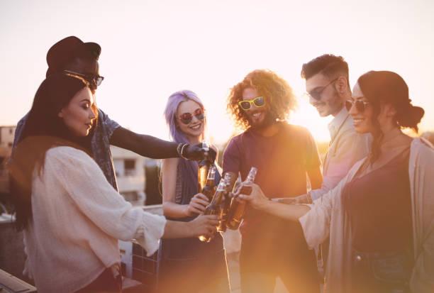 glückliche multiethnische freunden toasten mit getränken im sommer terrasse partei - dachgarten stock-fotos und bilder