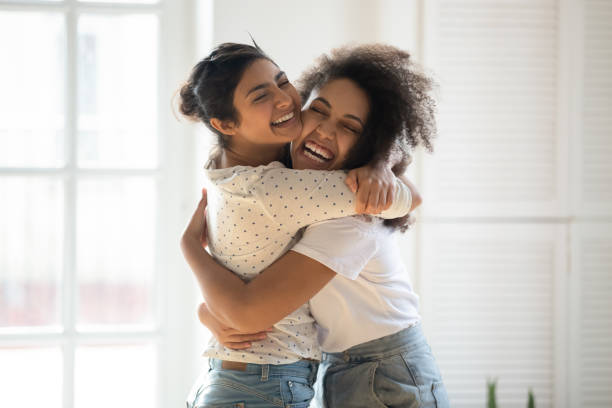 Happy multiethnic girlfriends have fun hugging indoors stock photo