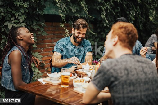 istock Happy multi-ethnic group of people laughing at the restaurant 699107178