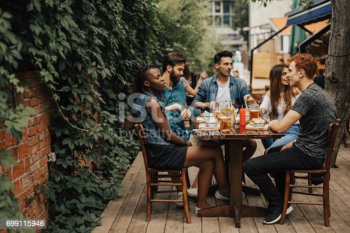 istock Happy multi-ethnic group of people sitting at the fastfood restaurant 699115946