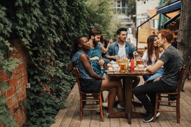 Feliz grupo multiétnico de pessoas sentadas no restaurante fastfood - foto de acervo