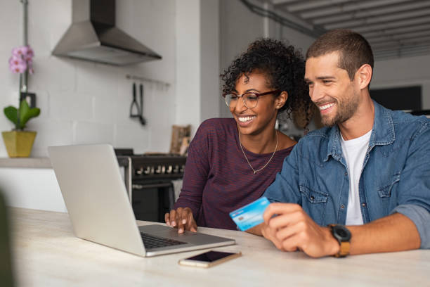 Happy multiethnic ouple making online payment Smiling young couple making shopping online with credit card and laptop at home. Happy multiethnic couple holding debit card while buying on ecommerce site using laptop. Cheerful guy and african girl making online purchase. home shopping stock pictures, royalty-free photos & images