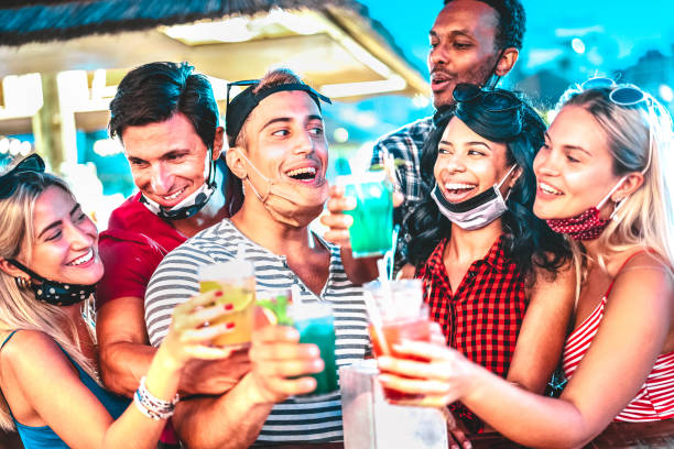 Happy multiethnic people drinking at night bar with open face masks - New normal summer concept with millenial friends having fun together - Focus on middle guy and girl with defocused background stock photo