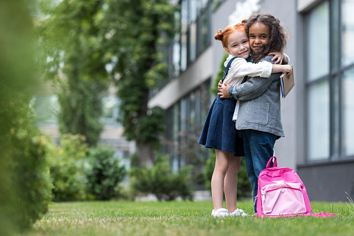 istock happy multiethnic schoolgirls hugging and smiling at camera while standing near school 834599578