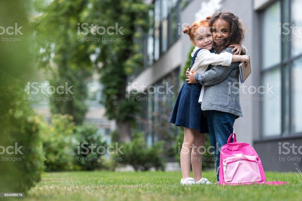 colegialas multiétnicas felices abrazándose y sonriendo a la cámara mientras está parado cerca de la escuela - foto de stock