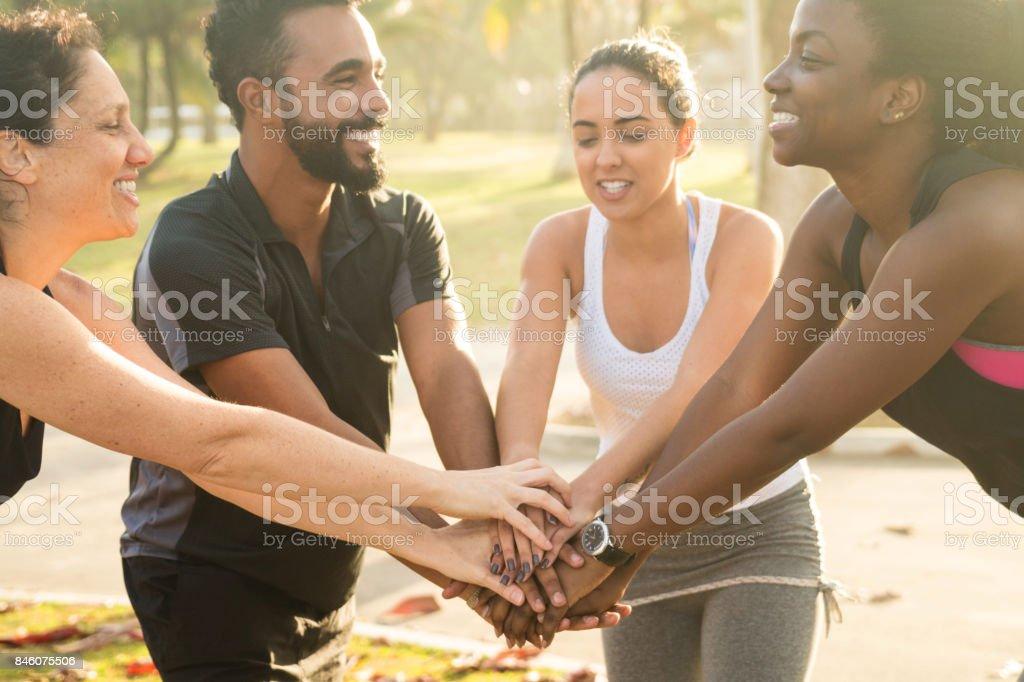Felizes amigos desportivos multi-étnica empilhamento mãos no parque - foto de acervo