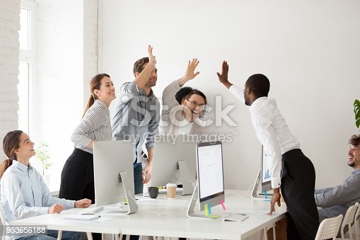 istock Happy multi-ethnic team giving high five together celebrating corporate success 953656188