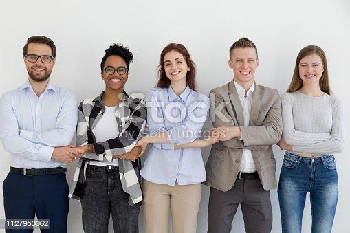 937843262 istock photo Happy multi-ethnic team people holding hands standing in row 1127950062