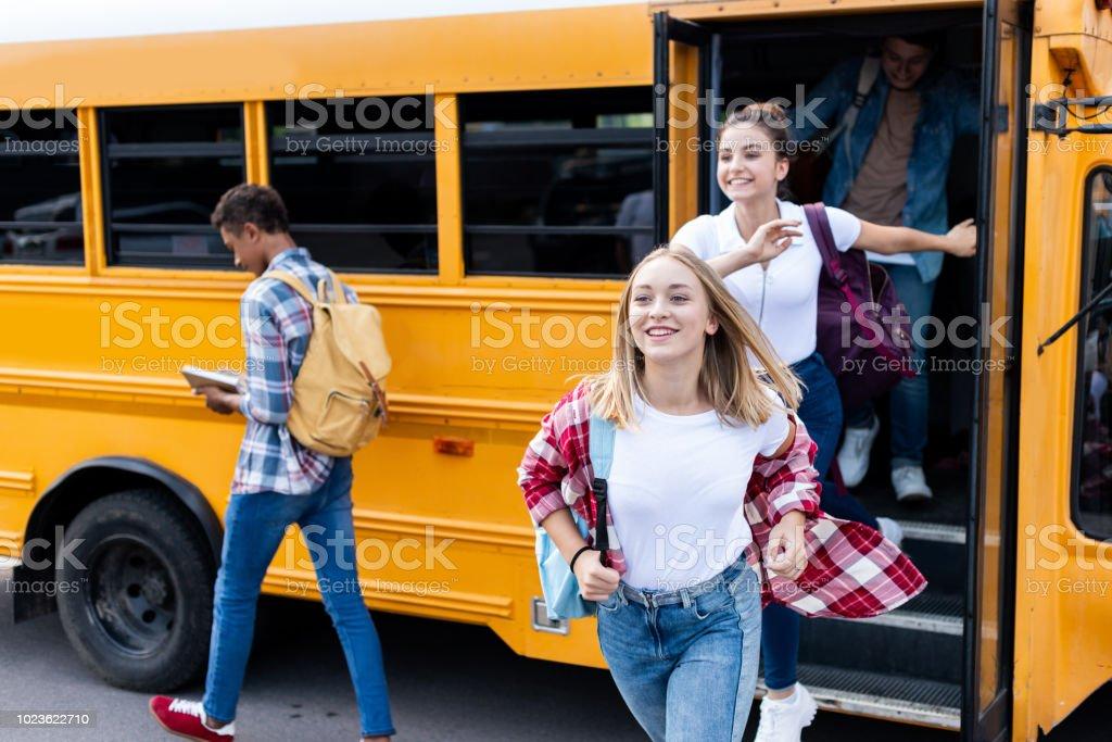 Happy multiethnic teen scholars running out school bus - Stock image .