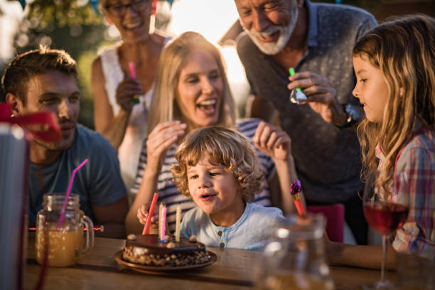 Happy multi-generation family celebrating boy's Birthday outdoors. Happy extended family celebrating little boy's Birthday outdoors. birthday candle stock pictures, royalty-free photos & images