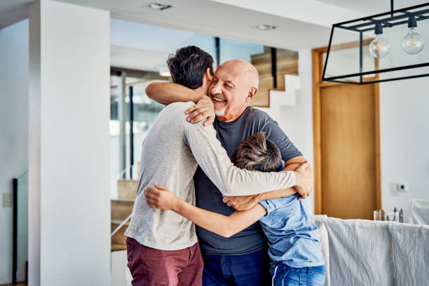 Happy multi-generation family embracing at home stock photo