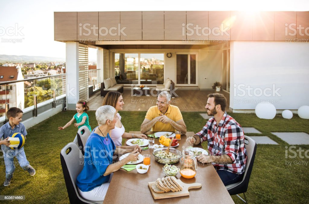 Happy multi-generation family enjoying during a meal on the balcony. stock photo