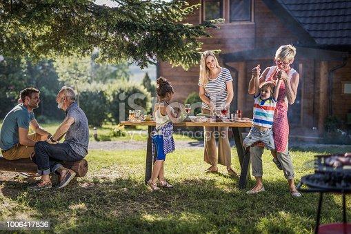 istock Happy multi-generation family enjoying in garden party in the backyard. 1006417836
