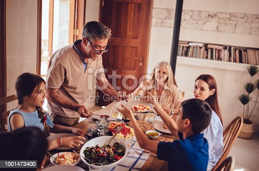 Happy multi-generation family with grandparents grandchildren and daughter having meal with grandfather serving food