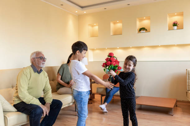 Happy Multi-Generation Family is Celebrating the Birthday of Cute Young Girl at Home. Cute Little Kid is Giving a Bouquet of Red Roses to his Young Sister. Cheerful Family is Sitting in the Living Room, Celebrating the Birthday Party and Listening to Young Girl Playing the Guitar. group of friends giving gifts to the birthday girl stock pictures, royalty-free photos & images