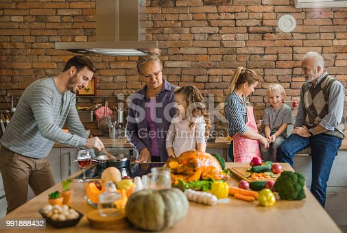 istock Happy multi-generation family preparing Thanksgiving dinner in the kitchen. 991888432