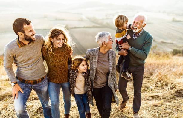 Mutlu çok nesilli aile sahada yürüyüş yaparken konuşuyor. stok fotoğrafı