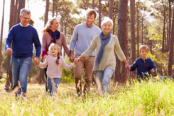 happy multi-generation family walking in the countryside - aktiva pensionärer utflykt bildbanksfoton och bilder