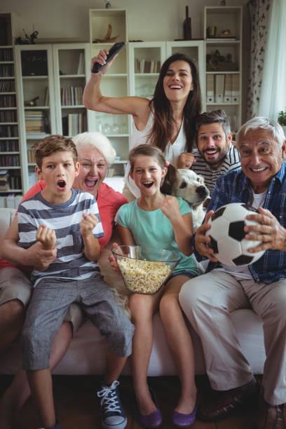 glücklich-mehrgenerationen familie beobachten fußballspiel im fernsehen im wohnzimmer - fußball themenzimmer stock-fotos und bilder