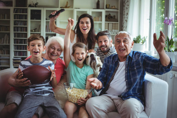 Happy multi-generation family watching soccer match on television in living room stock photo