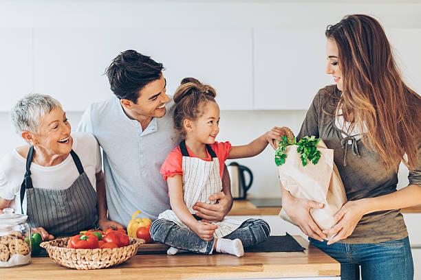 happy multi-generation family with groceries - kinderküche zubehör stock-fotos und bilder