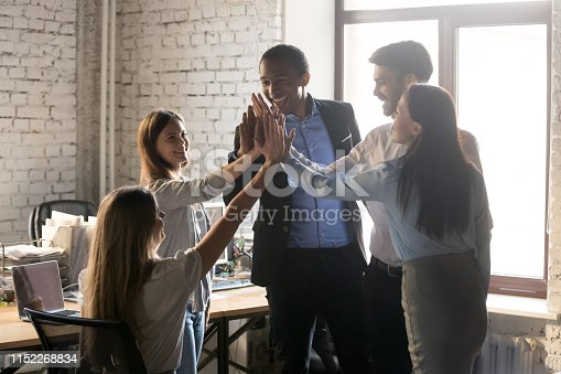 509032417 istock photo Happy multinational coworkers giving high five celebrating great teamwork result 1152268834