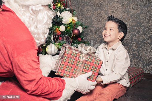 istock Happy multiraceal boy and Santa Claus with big gift box 497003176