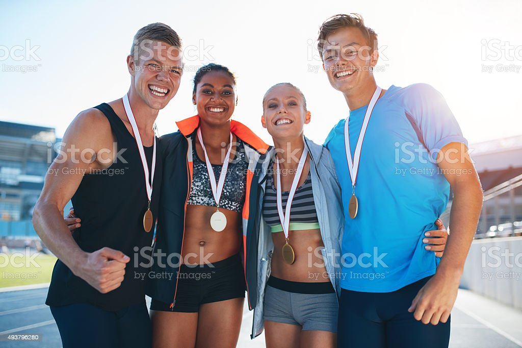 Happy multiracial athletes celebrating victory stock photo
