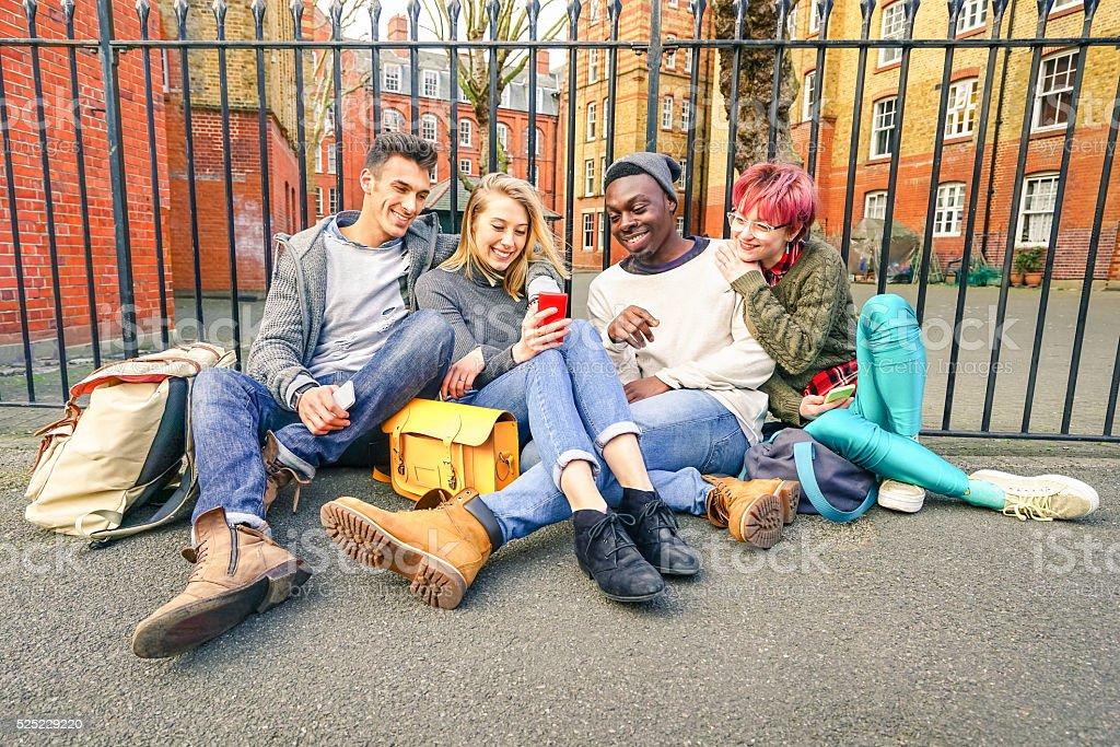 Happy multiracial best friends having fun using mobile smart phone stock photo