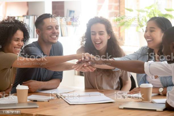 Happy Multiracial Business People Colleagues Stacking Hands Motivated By Success Stock Photo - Download Image Now