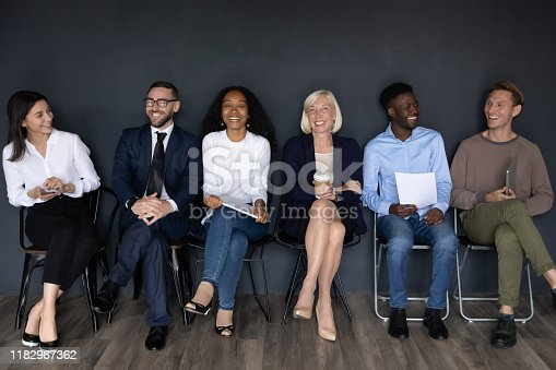 Happy multiracial professional business people young and old applicants group sit on chairs laughing having fun wait for job interview sit in row queue, human resource, staffing employment concept