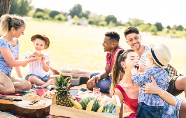glückliche multiethnischen familien spaß mit kindern bei picknick grill party - multikulturelle glück auf freude und liebe konzept mit gemischten rennen menschen spielen mit kindern im park - warme helle filter - kinder picknick spiele stock-fotos und bilder