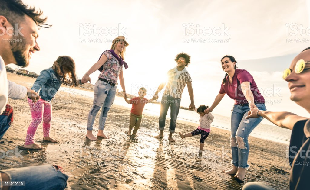 Happy multiracial families round dancing at the beach on ring around the rosy style - Multicultural happiness joy concept with mixed race people having fun outdoor at sunset - Vintage backlight filter stock photo