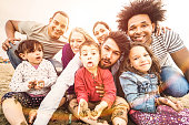 Happy multiracial families taking selfie at beach making funny faces - Multicultural happiness joy and love concept with mixed race people having fun outdoor at sunset - Bright pastel backlight filter