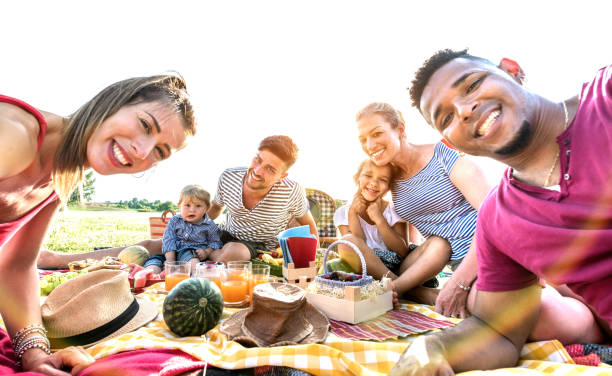 Happy multiracial families taking selfie at pic nic garden party Happy multiracial families taking selfie at pic nic garden party - Multicultural joy and love concept with mixed race people having fun together at sunset picnic barbecue - Warm vivid sunshine filter family bbq stock pictures, royalty-free photos & images