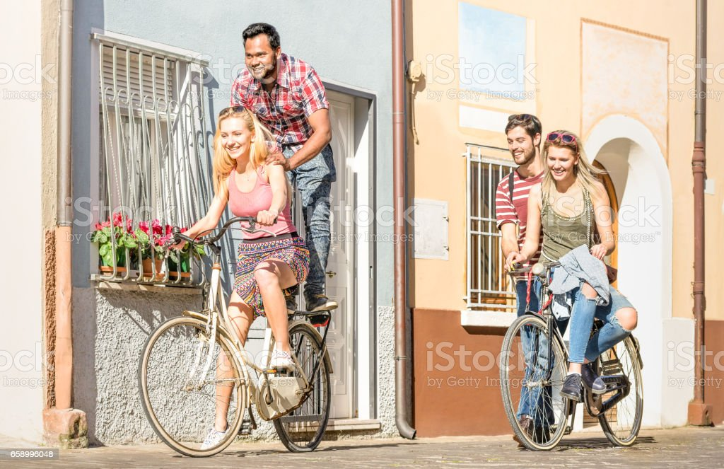 Happy multiracial friends couple having fun riding bicycle in city old town - Friendship concept with multicultural young people on funny attitude biking together - Warm afternoon color tone filter royalty-free stock photo