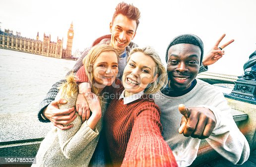 Happy multiracial friends group taking selfie in London at european trip - Young people addicted by sharing stories on social network community - Millennials lifestyle concept on vivid contrast filter