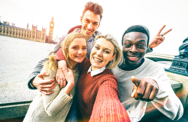 Happy multiracial friends group taking selfie in London at european trip - Young people addicted by sharing stories on social network community - Millennials lifestyle concept on vivid contrast filter Happy multiracial friends group taking selfie in London at european trip - Young people addicted by sharing stories on social network community - Millennials lifestyle concept on vivid contrast filter generation z stock pictures, royalty-free photos & images