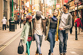Happy multiracial friends walking on Brick Lane at Shoreditch London - Friendship concept with multicultural young people on winter clothes having fun together - Soft focus with warm contrasted filter
