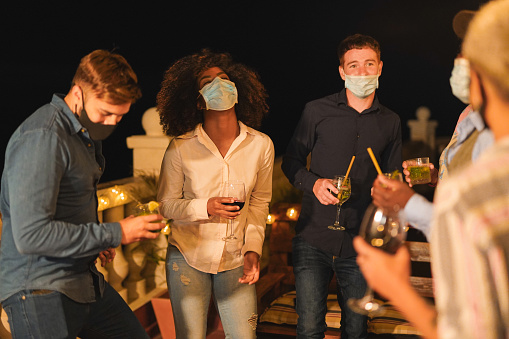 Happy multiracial friends with cocktails dance outdoor while wearing surgical face mask - Coronavirus alternative lifestyle