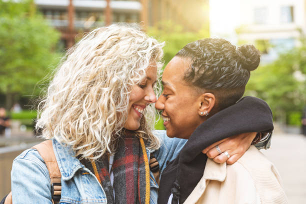 Happy multiracial girlfriends in love embracing Happy multiracial girlfriends in love embracing and cuddling - Lesbian couple, millennials women, girls in London living happy lifestyle - LGBTQ concept with mixed race beautiful couple gay couple stock pictures, royalty-free photos & images