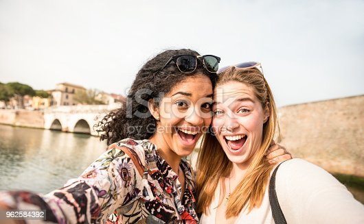 istock Happy multiracial girlfriends taking selfie and having fun outddors - Friendship concept with girls at spring break travel - Modern lifestyle with female best friends women - Bright day filter tone 962584392