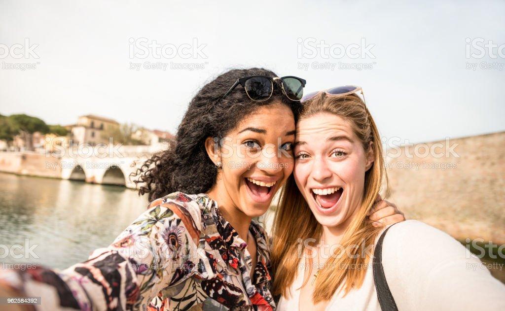 Heureuse copines multiraciales tirant selfie et s'amusant outddors - concept d'amitié avec des filles au voyage de la semaine de relâche - style de vie moderne avec des femmes d'amis meilleures femelle - brillant ton filtre jour - Photo