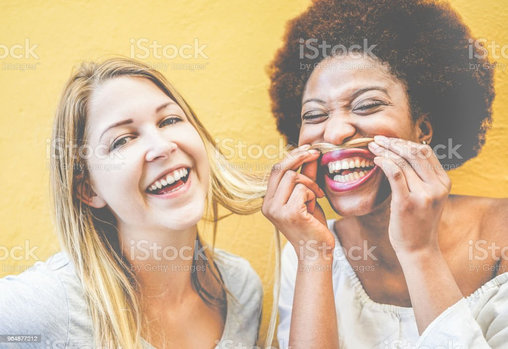 Happy multiracial millennials girls having fun together playing with hairs - Young trendy women laughing and smiling together - Youth lifestyle and friendship concept - Focus on females faces royalty-free stock photo