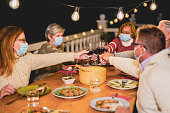 istock Happy multiracial senior people cheering with red wine at dinner while wearing surgical face mask for coronavirus 1280526363