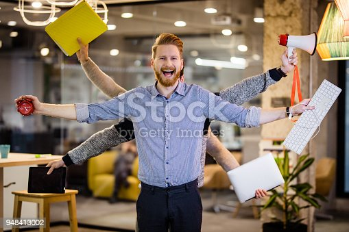 Happy redhead businessman with many hands standing in the office and looking at camera.
