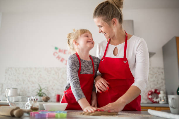 happy mum and daughter kneading dough together - christmas cooking foto e immagini stock